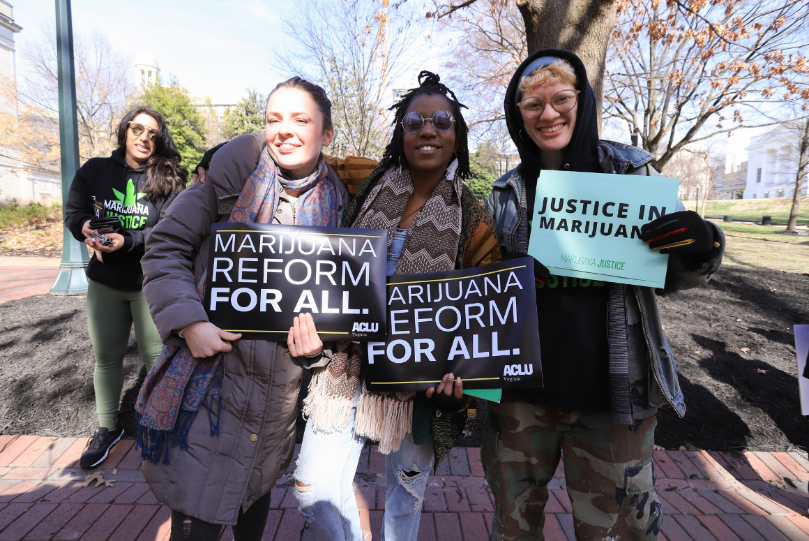 """Three advocates holding signs that say """"marijuana reform for all"""" and """"justice in marijuana"""""""
