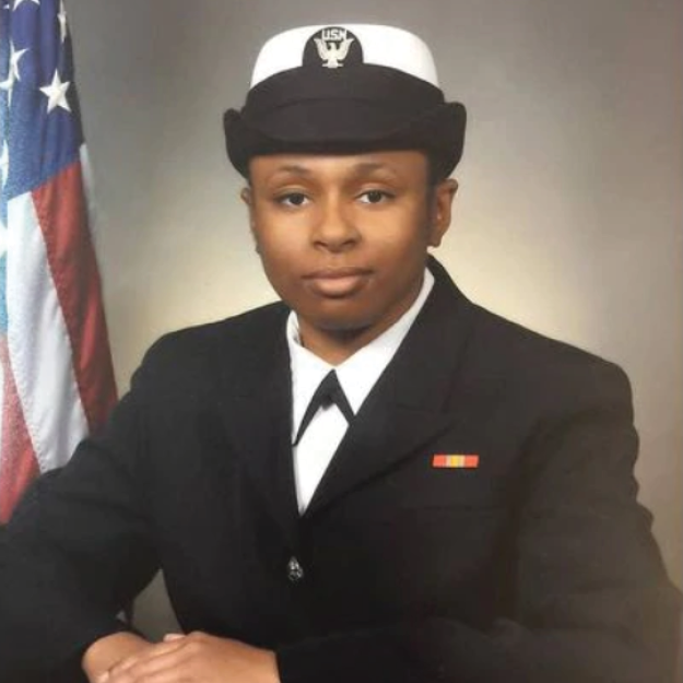 photo of India Kager, dressed up in a navy uniform with the U.S. flag in the background
