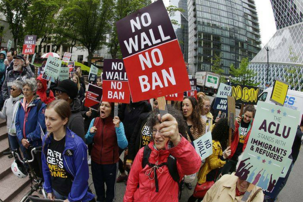 """People out on the street protesting, holding """"NO BAN NO WALL"""" signs"""