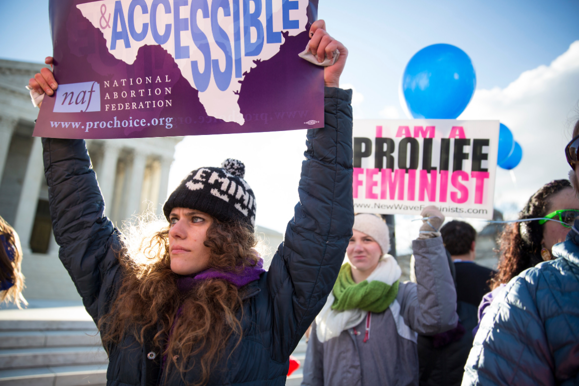 "A woman holding a sign of an American map with the word ""Accessible"" written across. She was protesting in front of the Supreme Court."