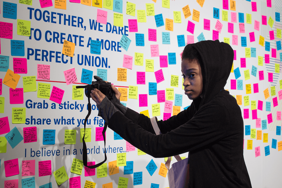 Stephanie Younger, a black student from Richmond, holding her camera in front of a wall covered in sticky notes in which people shared what they were fighting for at the ACLU National Membership Conference