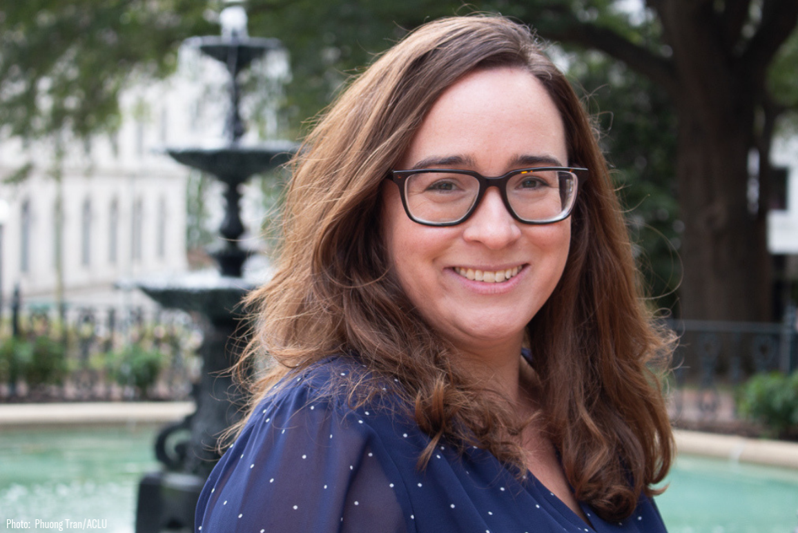 Profile picture of our Director of Philanthropy Alissa Aronovici, a middle aged woman with brown hair, glasses, and bright smile, with a fountain in the background
