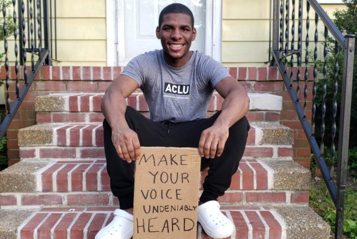 "a photo of our intern Alton Coston sitting on the steps in front of his house, holding a cardboard sign that says ""make your voice undeniably heard"""