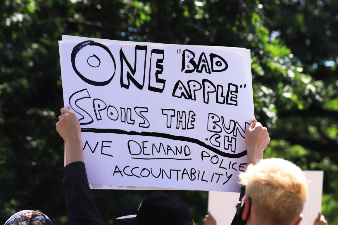 """protester hold a sign on white paper with black lettering: """"one bad apple spoils the bunch. We demand police accountability."""""""
