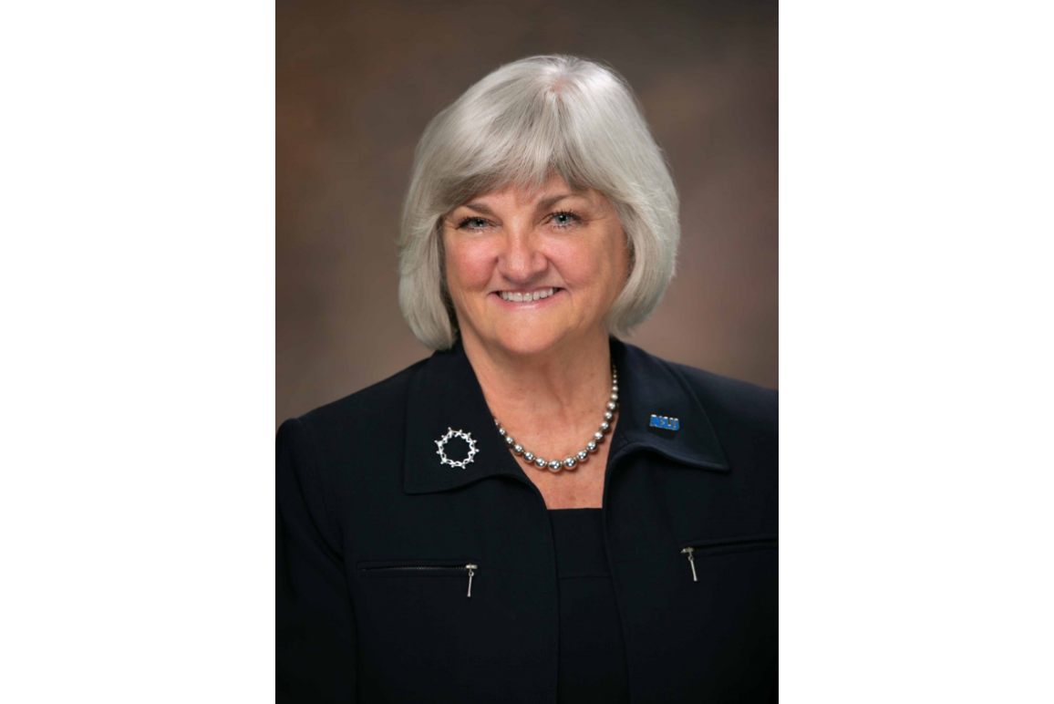 portrait of our executive director Claire Gastanaga, with shoulder length silver hair, round face, blue eyes, and wearing all black.