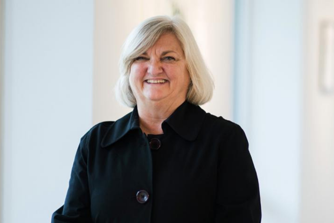 A picture of our Executive Director Claire Gastanaga, a middle-aged white woman with white hair, wearing a black shirt against a white background