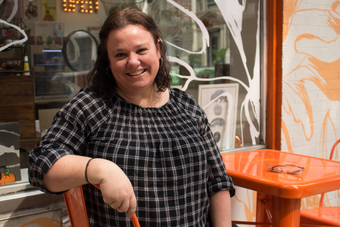 Profile picture of our Legal Director Eden Heilman, a middle-aged Caucasian women with brown hair and confident smile, sitting in front of a coffee shop