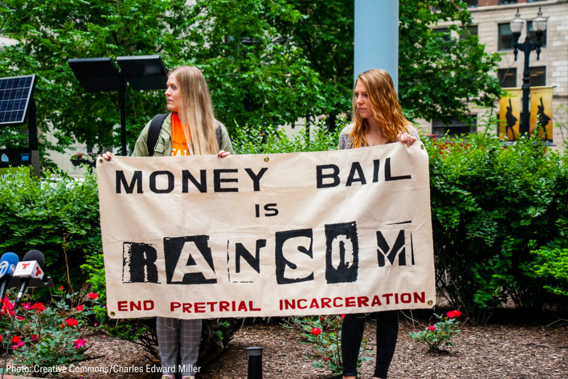 """two woman holding a banner that said """"money bail is ransom. End pretrial incarceration."""""""