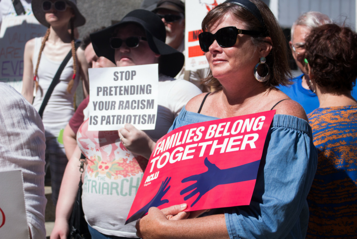 "A woman holding a sign that says ""Families Belong Together"" and another woman holding a sign that says ""Stop Pretending Your Racism is Patriotism"" in the background"