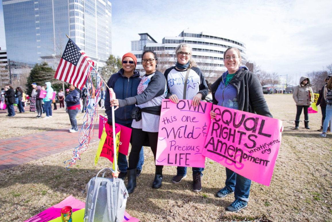 Four women of different races hold protest signs in support of the ERA