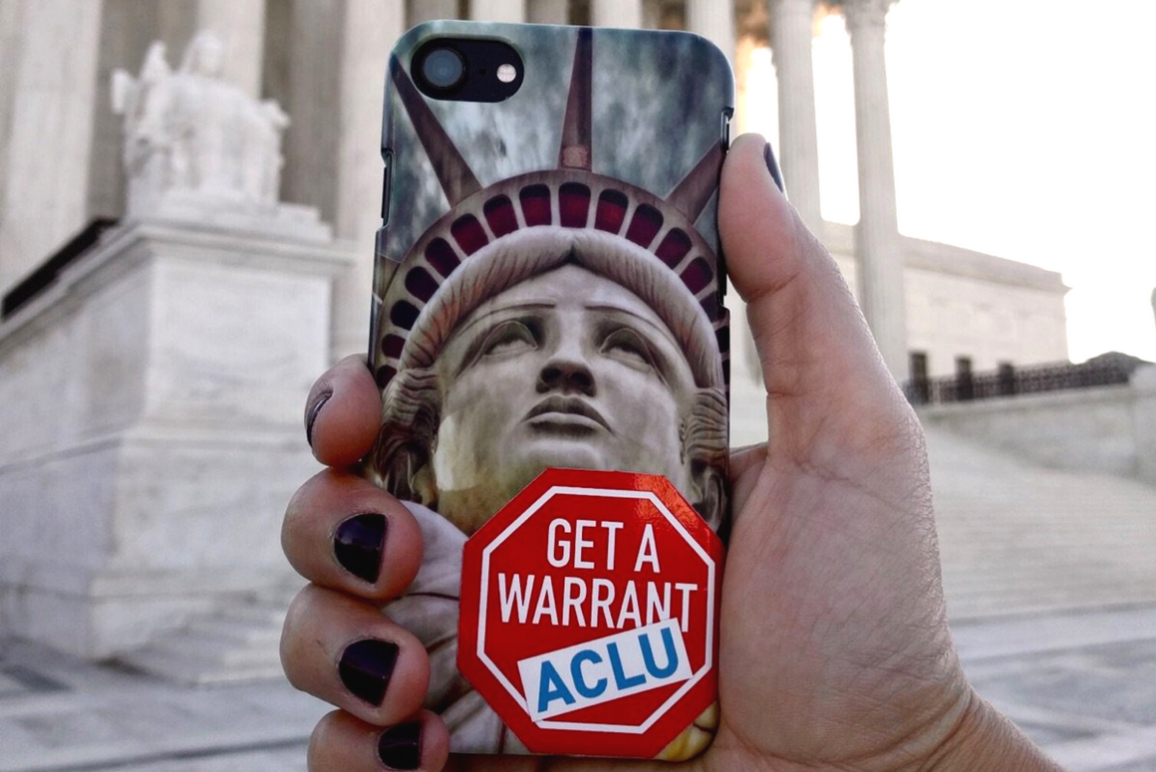 hand holding a phone with Lady of Liberty case and an ACLU Get a Warrant sticker