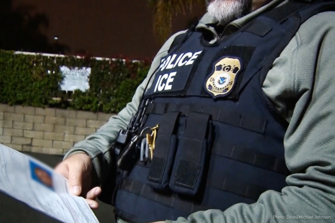 ICE agents holding a piece of paper