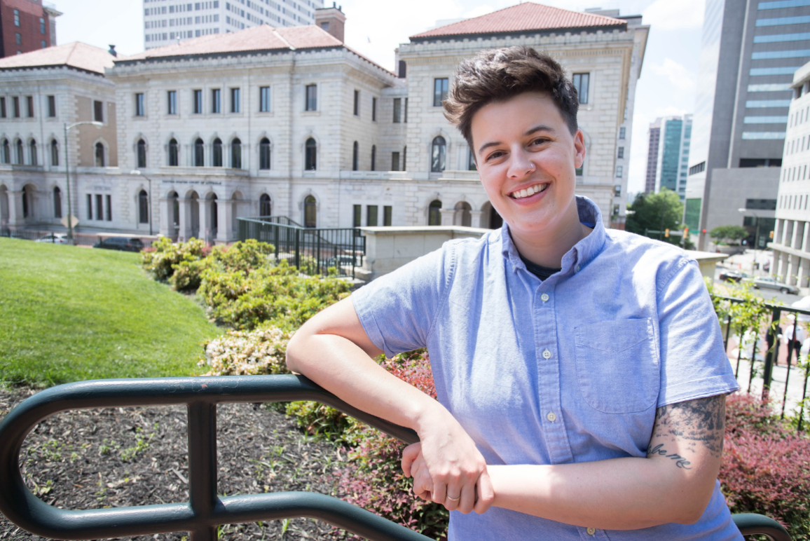 A photo of our director of finance and administration Jess Powers, young woman with short hair, bright smile, with a courthouse in the background