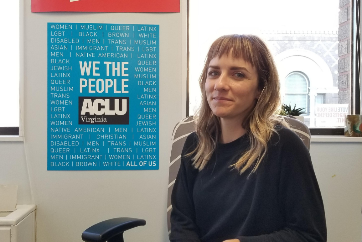 portrait of our client Katie Carline, a petite blonde woman with blue eyes wearing a navy blue sweater, next to an ACLU-VA poster