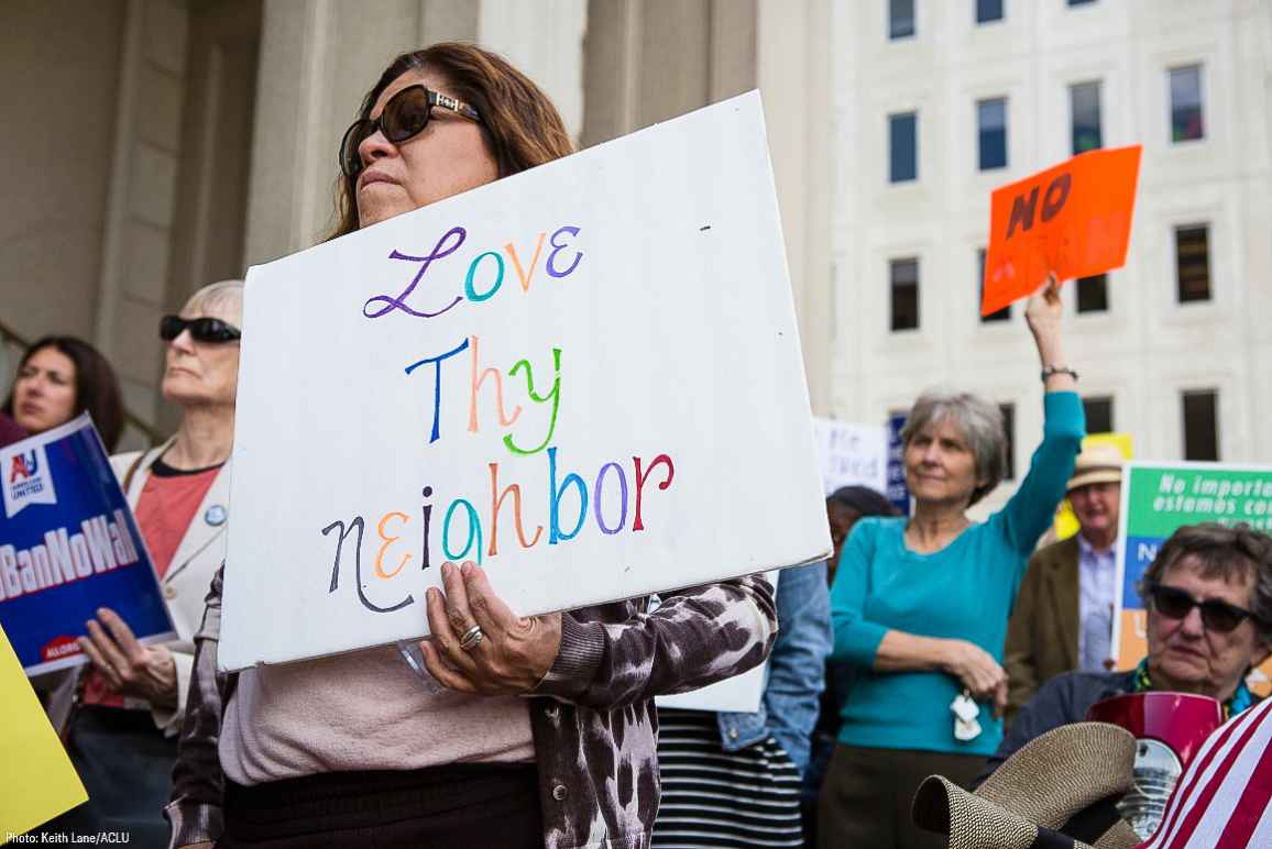 "A Latina woman holding a sign that says ""Love Thy Neighbor"""