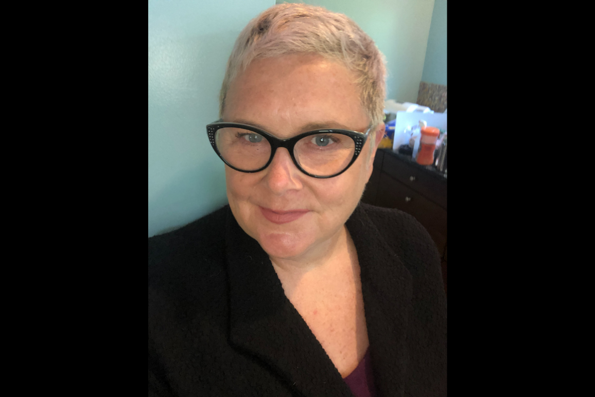 A photo of Mary, a white woman with pixie short blonde hair, wearing a pair of cat eye glasses.