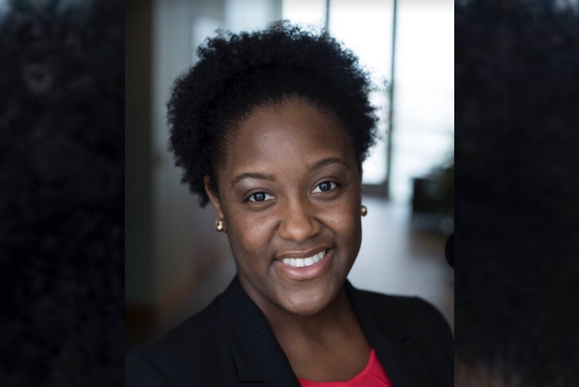 headshot of our Dunn Legal Fellow Monique Gillum, a black woman with short curly hair, wearing a black blazer with red blouse underneath.