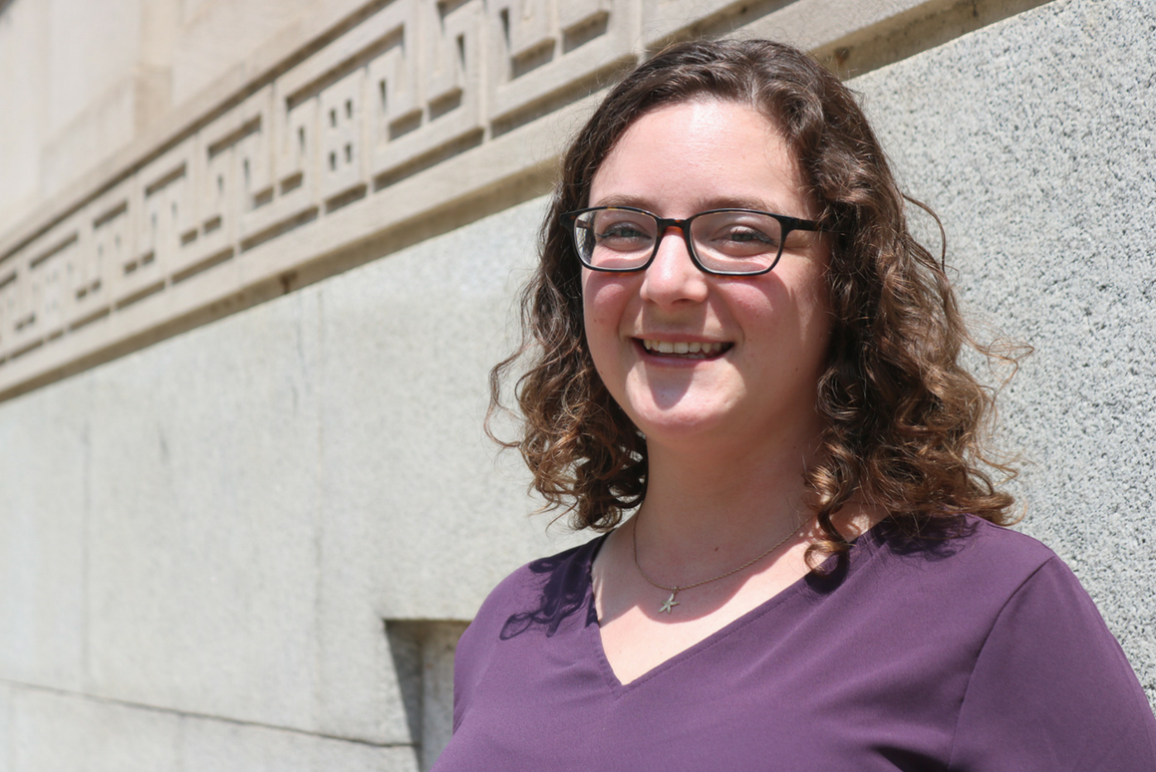 profile picture of our women's rights attorney Nicole Tortoriello, white woman, round face, curly brown hair, black-rimmed glasses