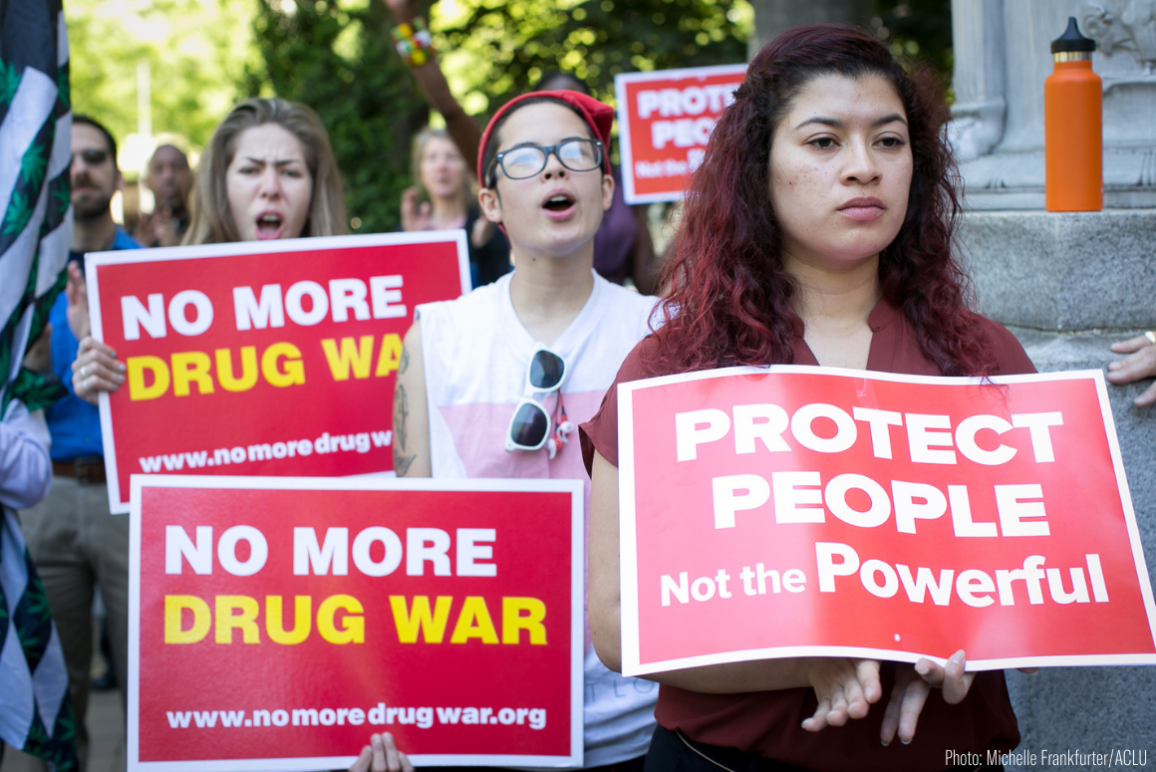 "protesters holding signs that say ""no more drug war"" and ""protect people not the powerful"""
