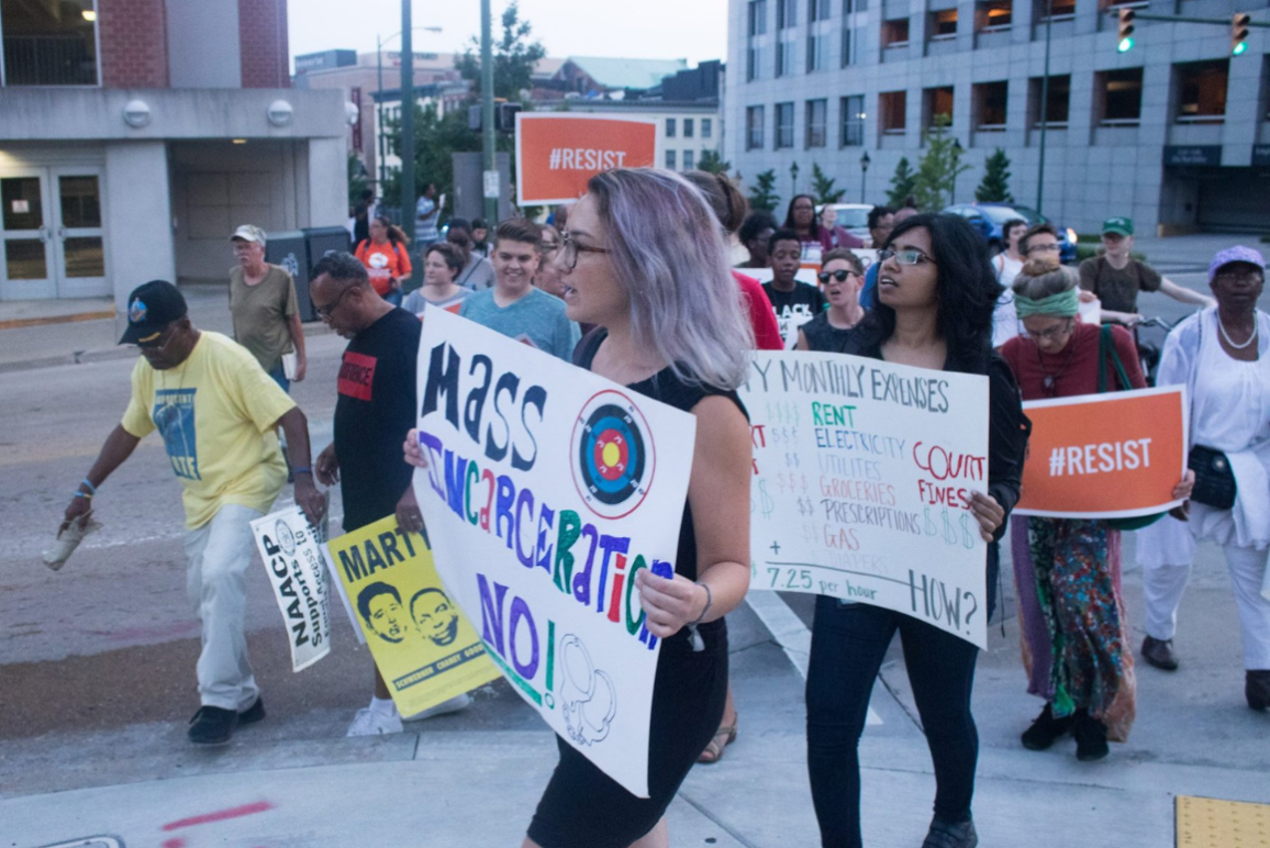 """A woman protester holding a sign that says """"Mass Incarceration NO!"""""""