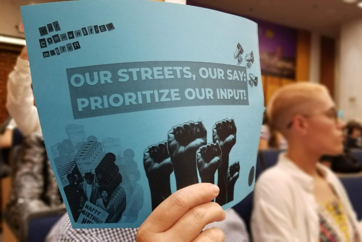 "blue sign with text that says ""our streets, our say: prioritize our input."""