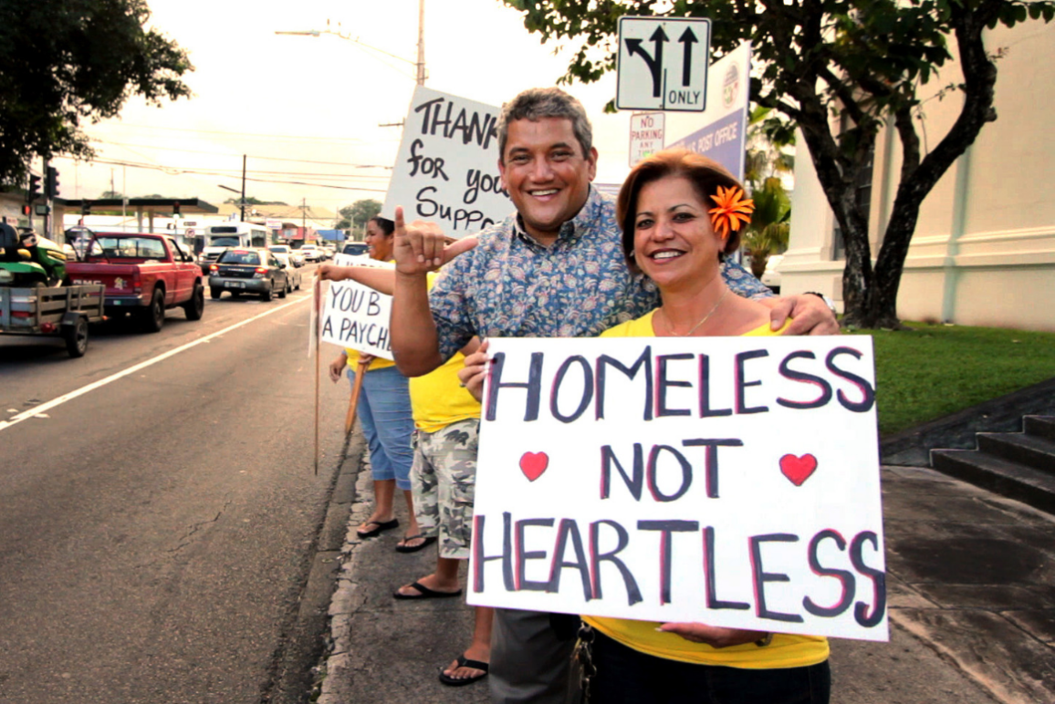 "A woman holding a sign that says ""Homeless not Heartless"""