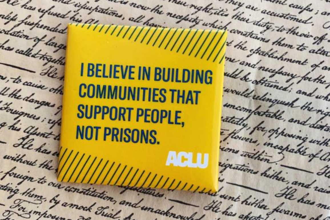 "a square yellow button with green text that says ""I believe in building communities that support people, not prisons"" against a background of cursive writing on parchment paper."
