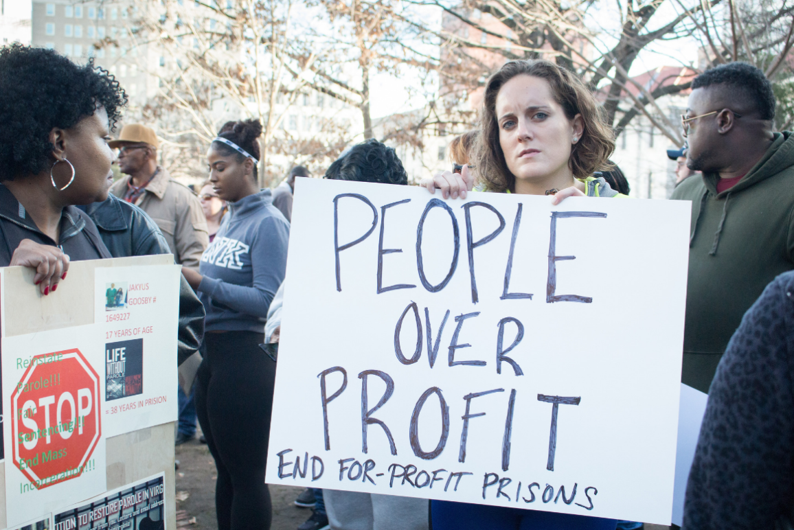 "a white woman holding a sign that says ""People Over Profit: End For-Profit Prisons)"