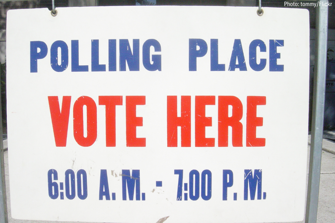 "a white sign with text in red and blue that says ""polling place vote here 6am to 7pm"""