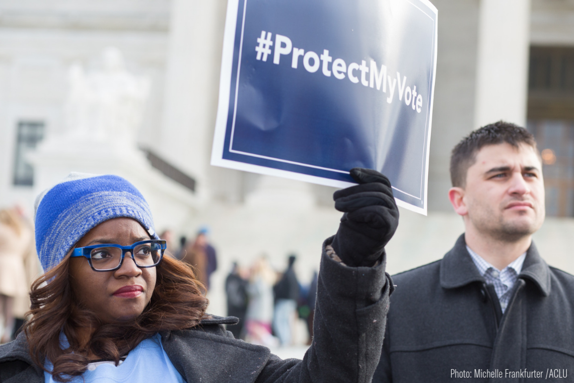 "A Black woman holding a sign that says ""Protect My Vote"""