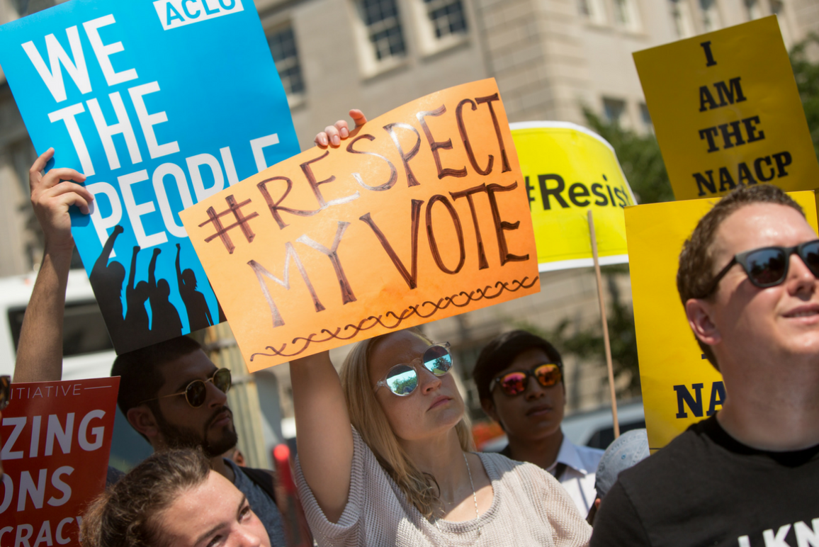 protesters holding signs that say Respect My Vote