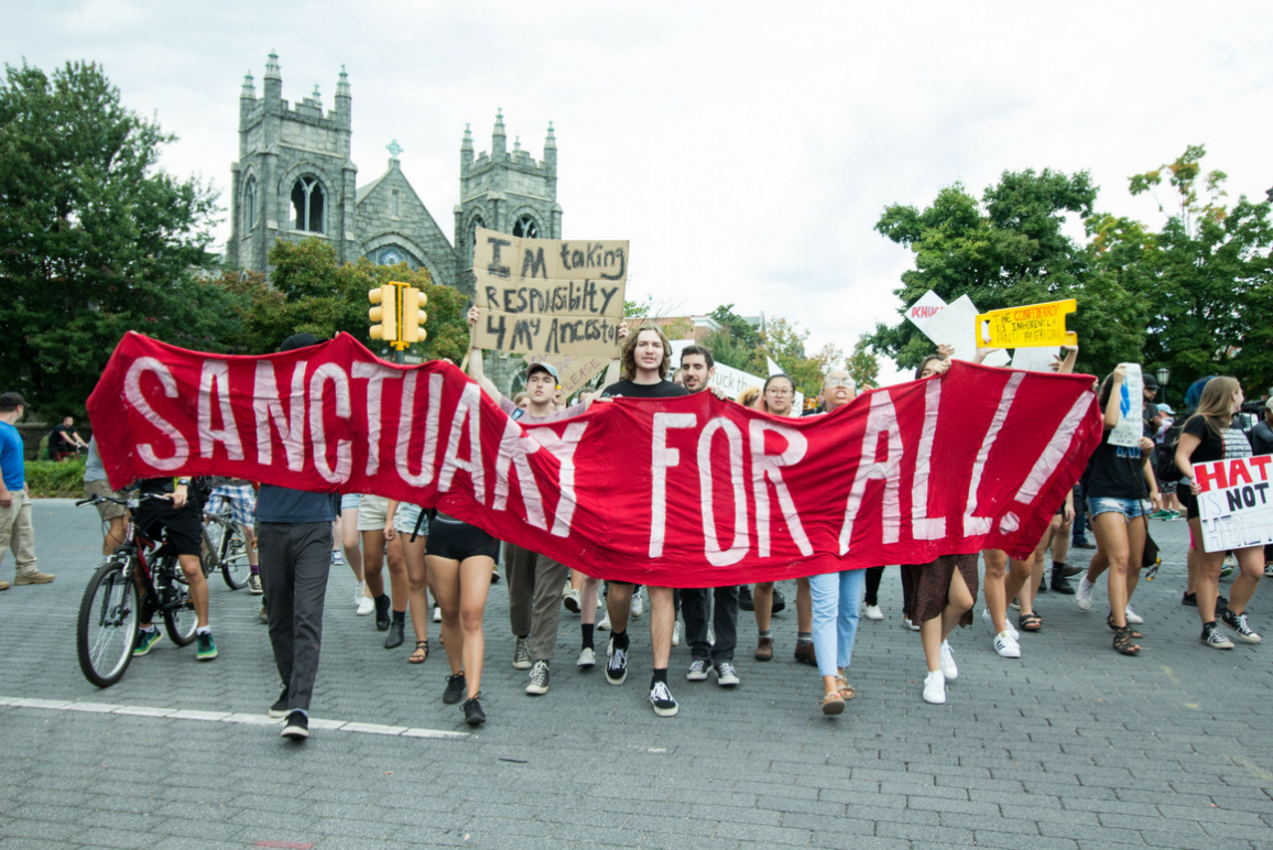 "A group of protesters carried a red banner that said ""Sanctuary For All!"""