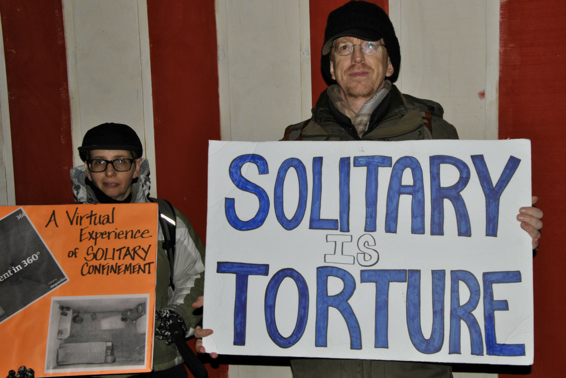 "A man holding a sign that says ""Solitary Is Torture"""