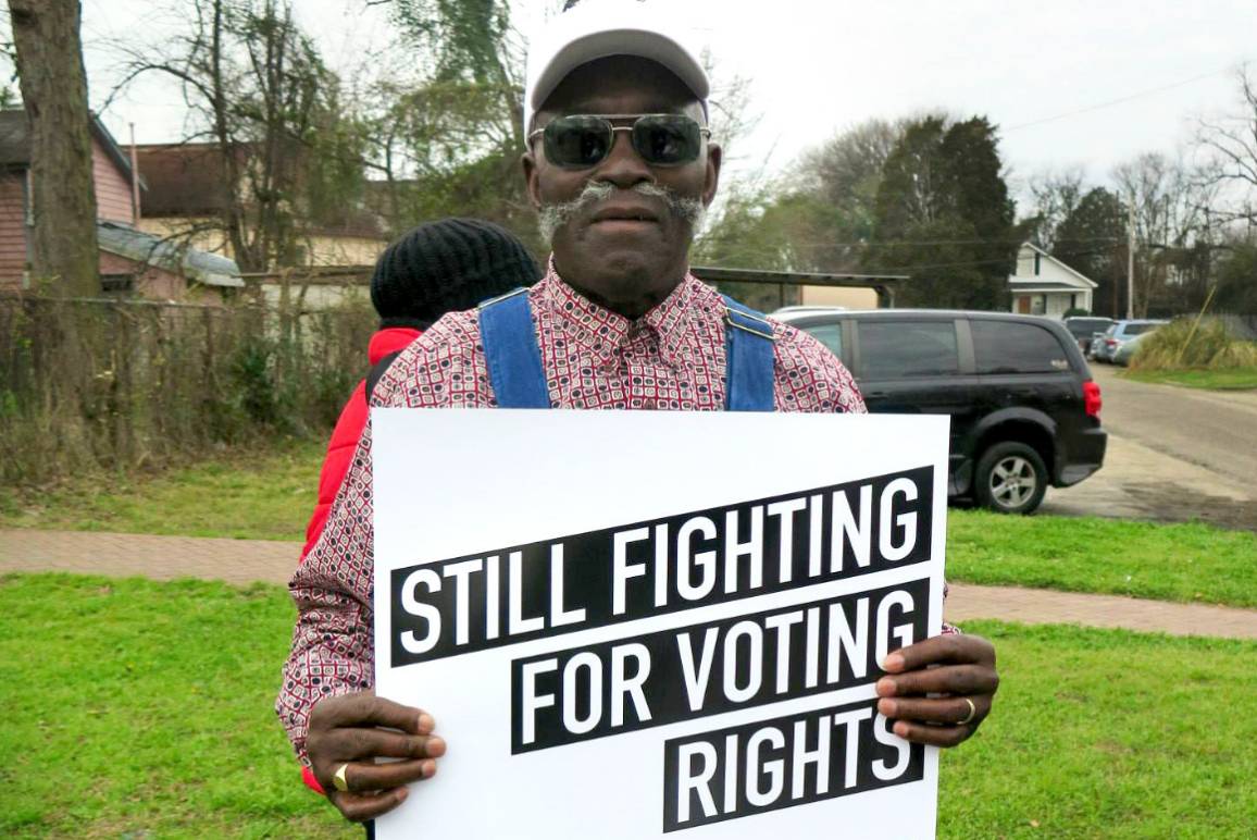 "a black man holding a protest sign that says ""Still Fighting for Voting Rights"""