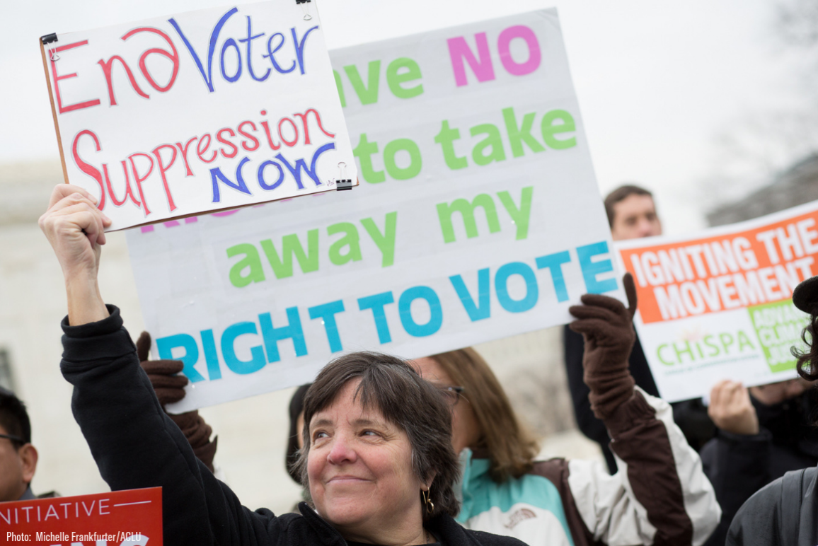 "A white woman holding a sign that says ""End Voter Suppression Now"""