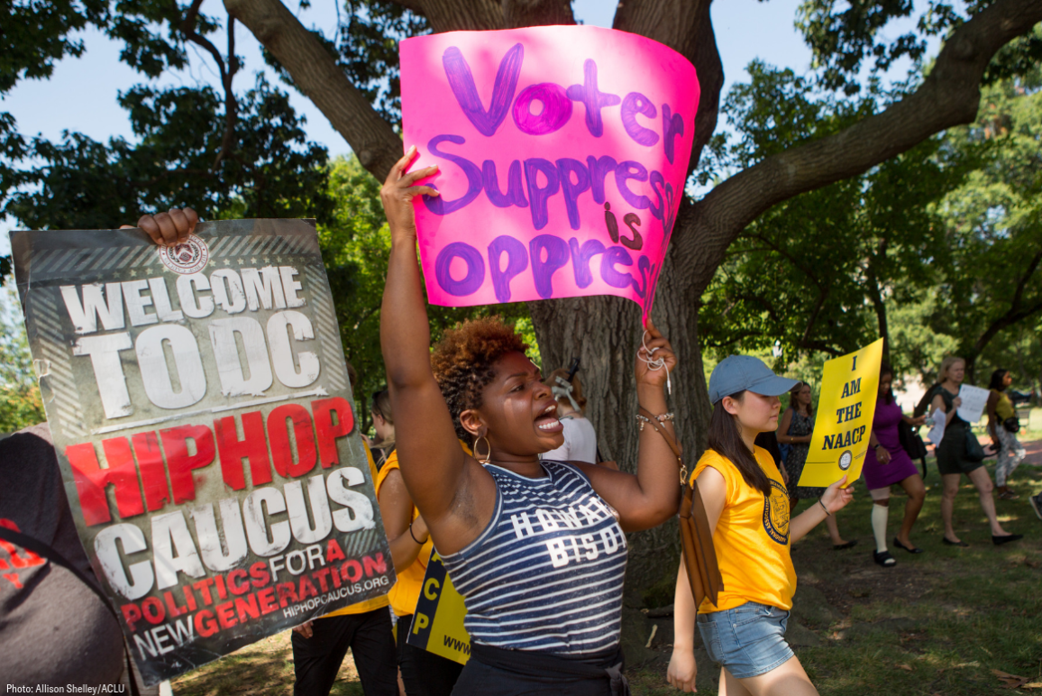 A black protester holding a sign that said voter suppression is oprression