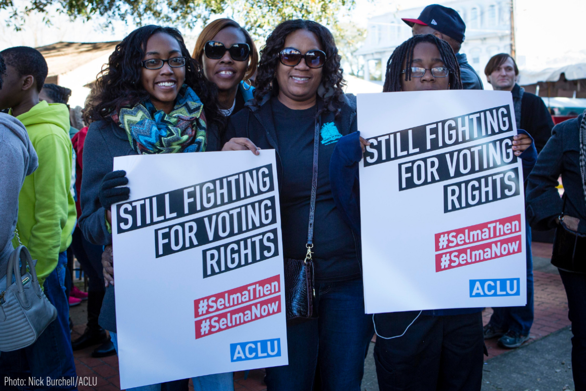 "A group of black women holding signs that say ""Still fighting for voting rights"""