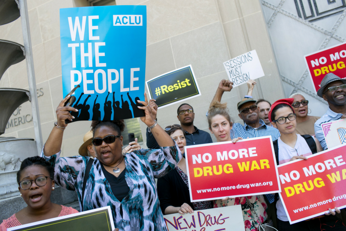 """People holding signs that say """"No More Drug War"""" and """"We The People"""""""