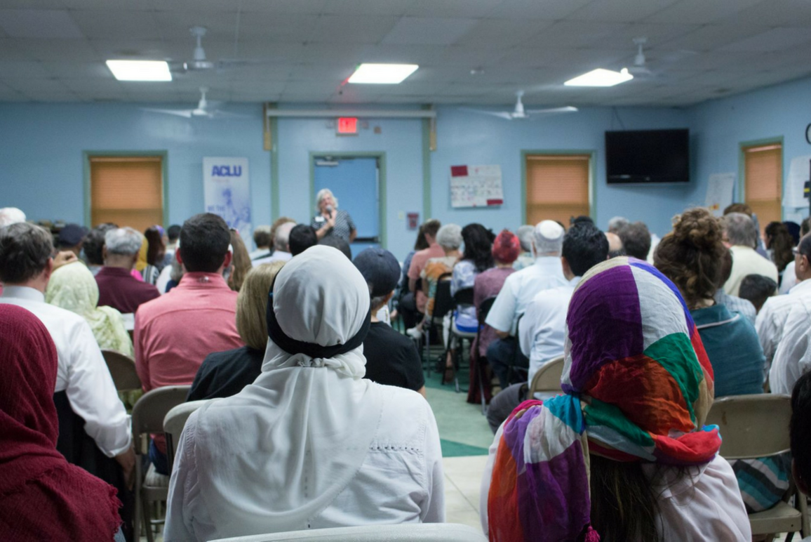 Picture from our No Muslim ban Community Forum in RIchmond, a roomful of people with our executive director speaking far in the back
