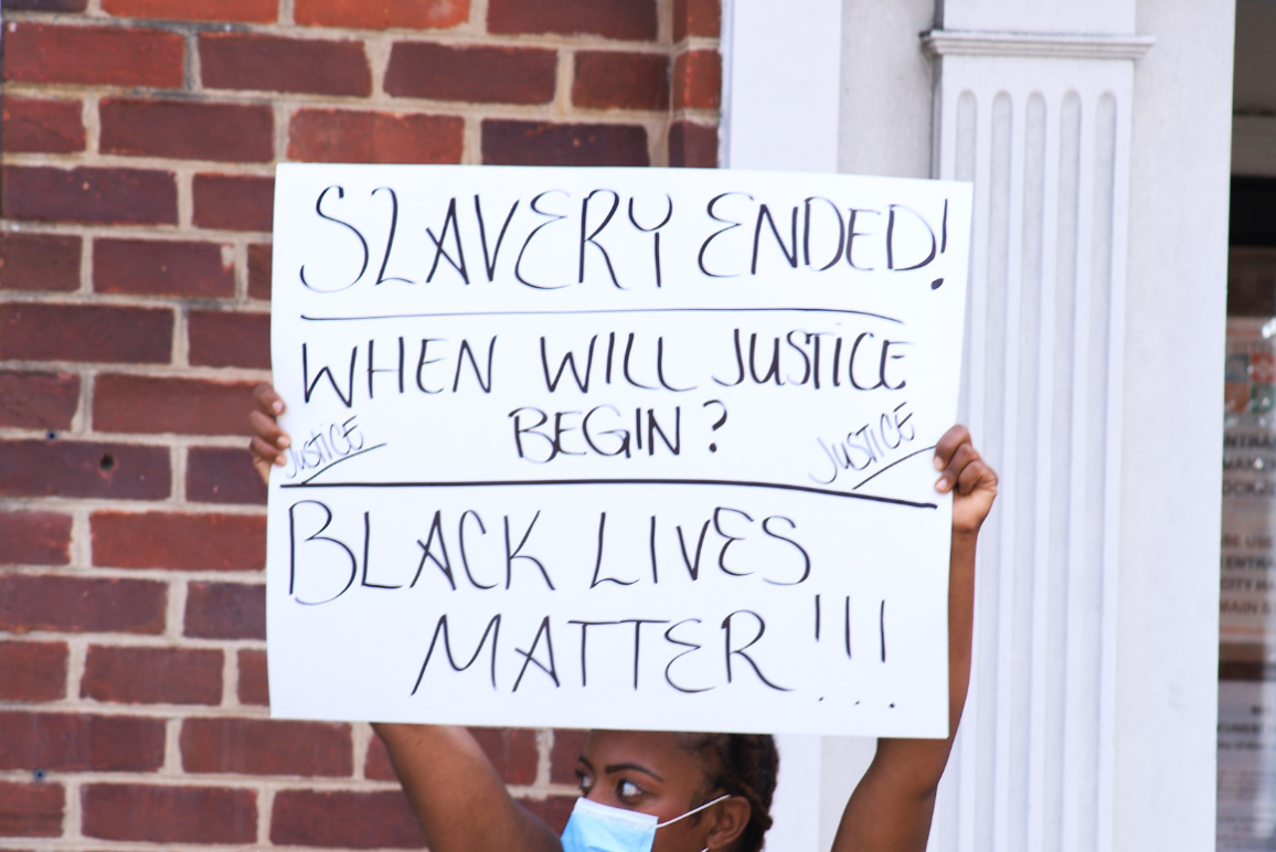 "Black woman holding a protest sign that says ""slavery ended, when will justice begin? Black lives matter!!!{"""