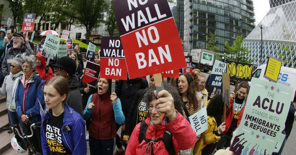 "People out on the street protesting, holding ""NO BAN NO WALL"" signs"