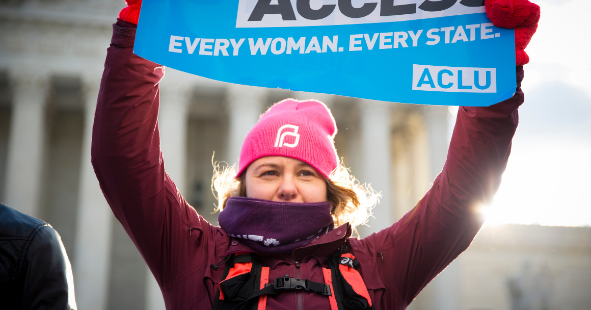 """A white woman holding an ACLU branded sign that said """"Abortion Access. Every Woman. Every State."""""""
