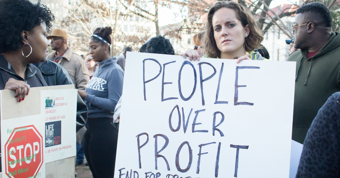 """a white woman holding a sign that says """"People Over Profit: End For-Profit Prisons)"""