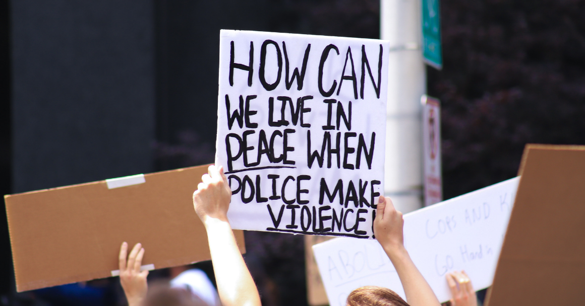 "a protest sign with the text ""how can we live in peace when police makes violence"""