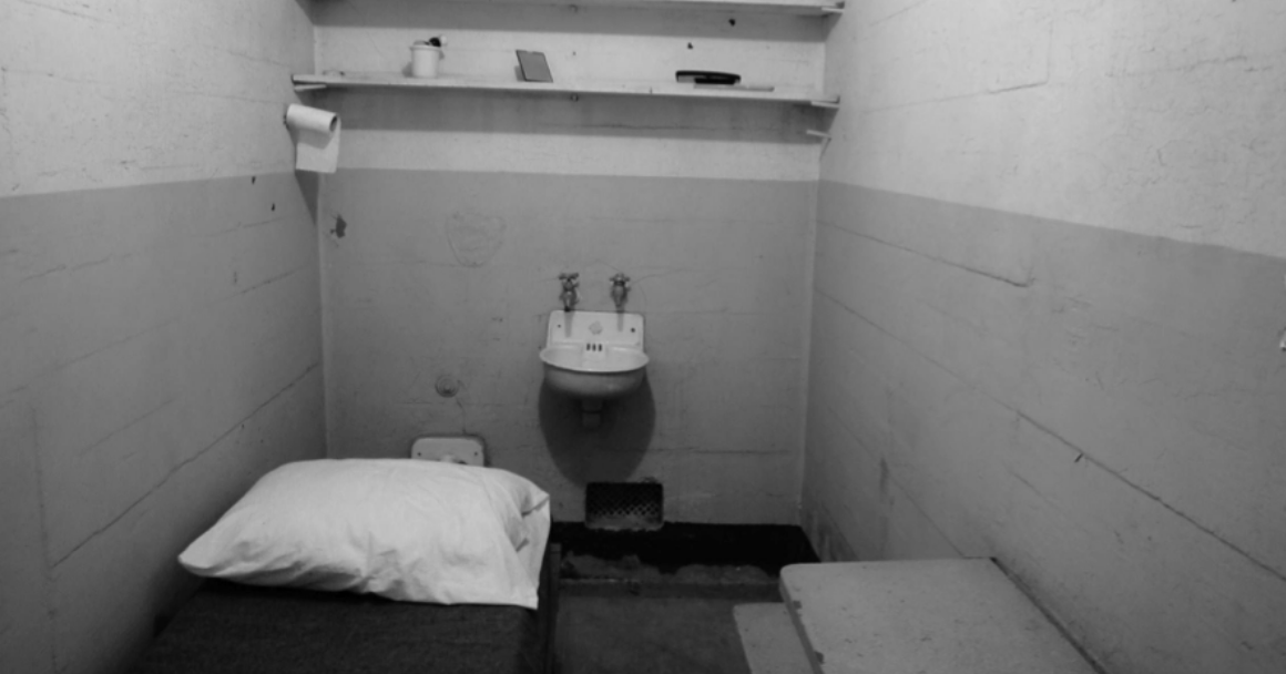 A black and white photo of a solitary confinement cell that is incredibly narrow, with one sink, a bed, and a shelf