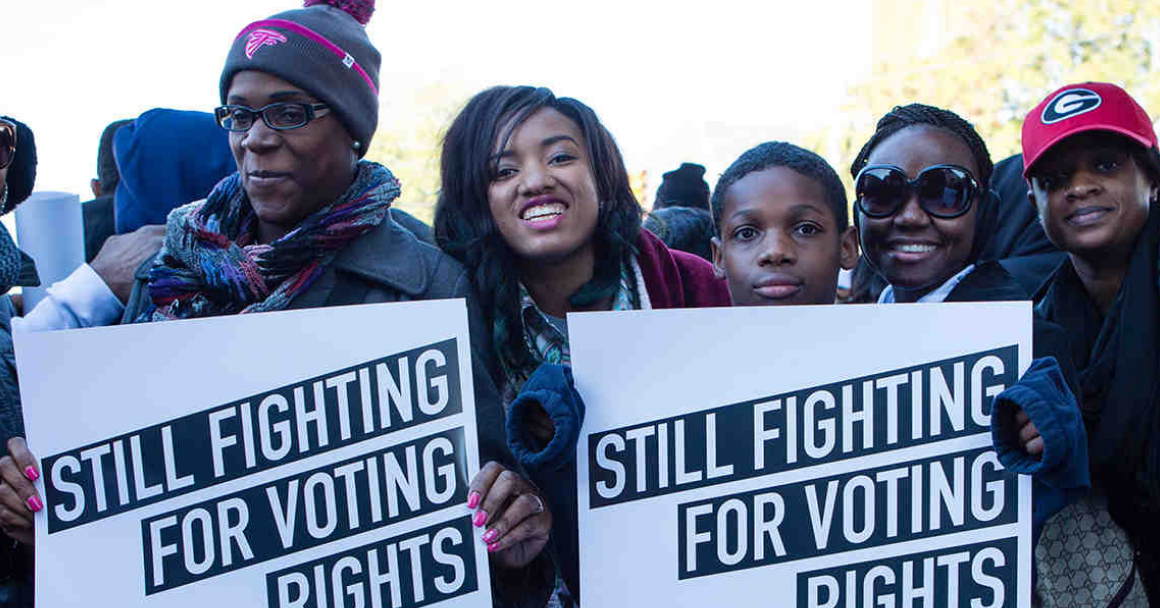 """a group of black voters held signs that say """"still fighting for voting rights"""""""