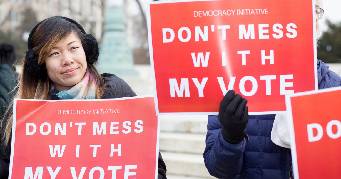 """A woman holding a red sign with white text that says """"Don't Mess With My Vote"""""""
